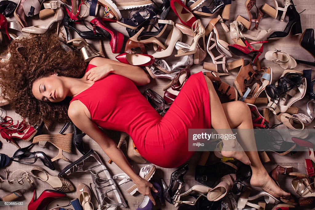 Young fashionable woman lying over stack of shoes : Stock Photo