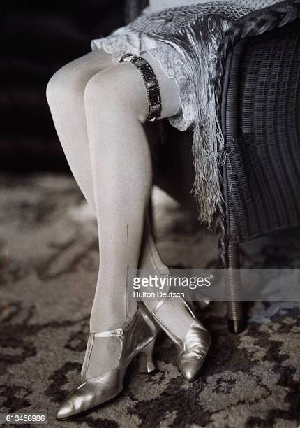 A young fashionable woman of the 1920s wears the latest from Paris a metal garter coordinated with metallic shoes with a Louis heel and patterned...