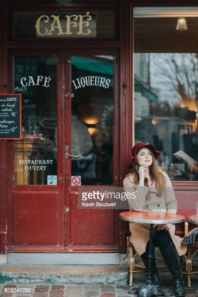 young fashionable woman sits outside a cafe along the streets of paris - french culture stock pictures, royalty-free photos & images
