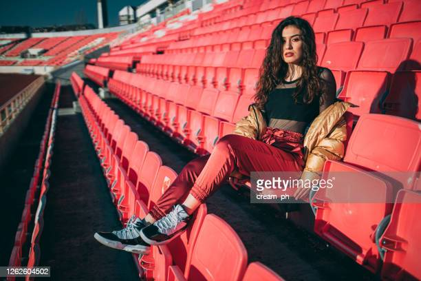 young fashionable woman sitting in an empty stadium - audience free event stock pictures, royalty-free photos & images