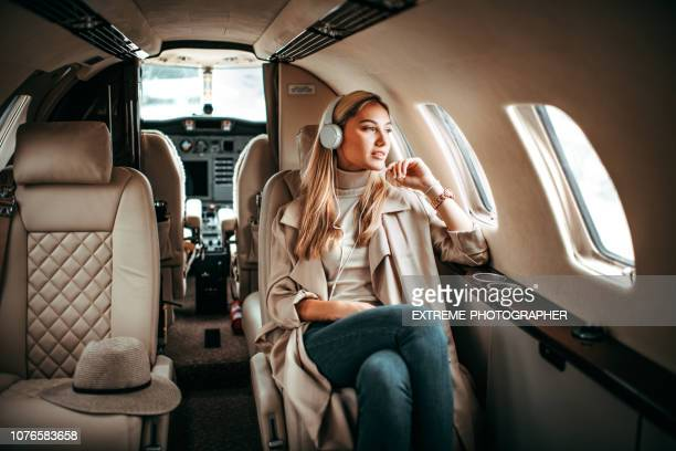 young fashionable woman sitting on a private airplane and listening to music through headphones - private aeroplane stock pictures, royalty-free photos & images