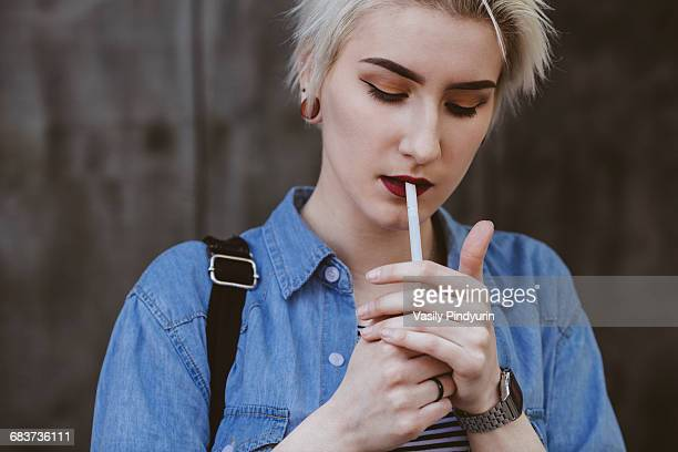 Young fashionable woman smoking cigarette while standing outdoors