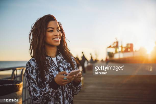 young fashionable woman texting on her phone in santa monica, la - white jacket stock pictures, royalty-free photos & images