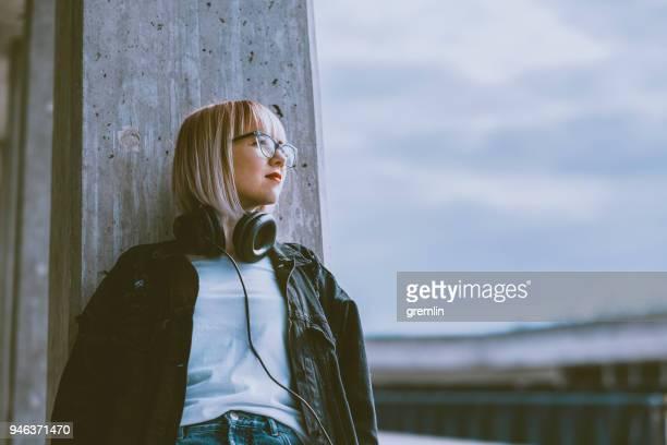 junge modebewusste frau mit skateboard - introspektion stock-fotos und bilder