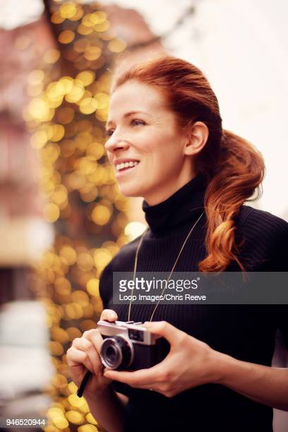 Young fashionable women with classic camera in front of lights in New York city