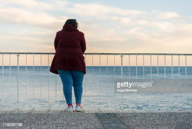 young fat woman standing alone on the beach - chubby stock pictures, royalty-free photos & images