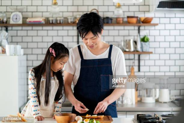 young father and daughter cooking together at home - jgalione stock pictures, royalty-free photos & images