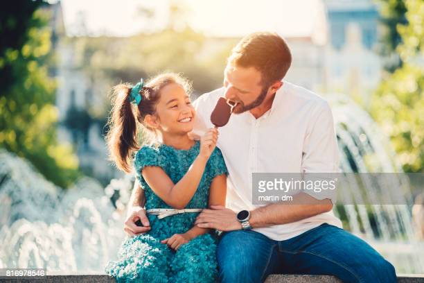 young father and daughter eating ice-cream at the fountain - bulgarian girl stock photos and pictures