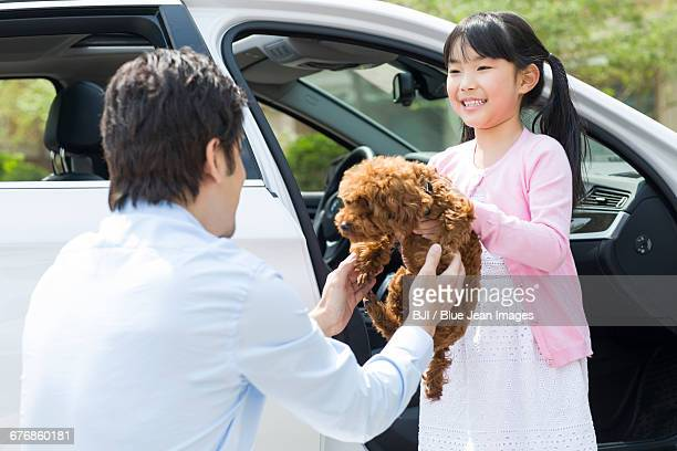 Young father and daughter getting out of car with their pet dog