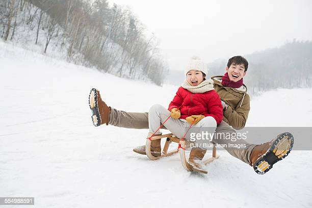 Young father and daughter sliding on a sled