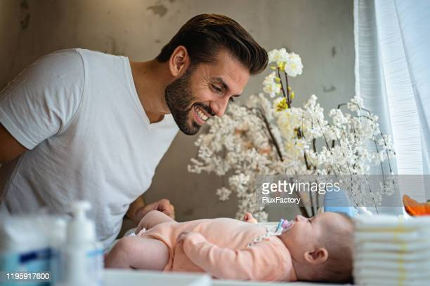 young father and his cute newborn daughter in nursery - baby changing mat stock pictures, royalty-free photos & images