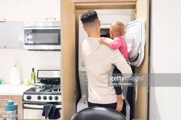 Young father and infant daughter at home