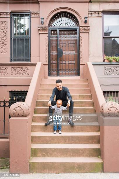 Young father and infant daughter on stoop in their city neighborhood