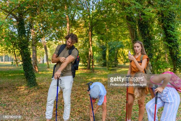 a young father and mother with children are traveling with backpacks and have problems with insects in the forest. - insect bites images stock pictures, royalty-free photos & images