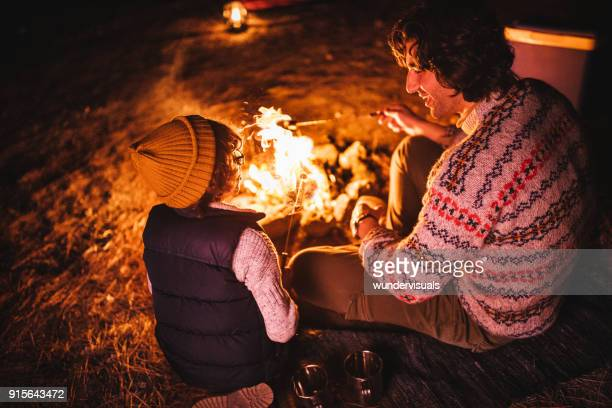 young father and son camping and roasting marshmallows over bonfire - bonfire stock photos and pictures