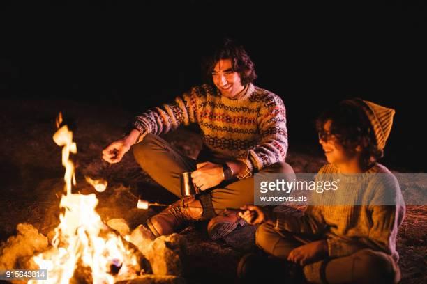 若い父親と息子キャンプ、キャンプファイヤーでマシュマロを焙煎 - アウトドアファイヤー ストックフォトと画像