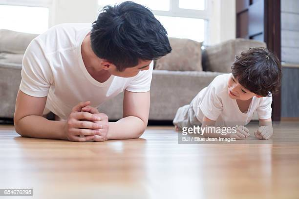 Young father and son exercising at home