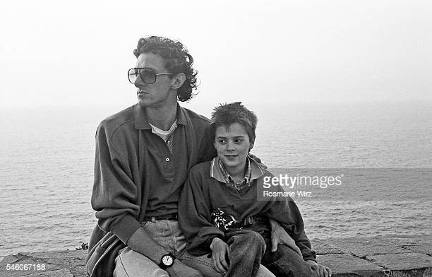Young father and son sitting in front of sea, spring 1983.