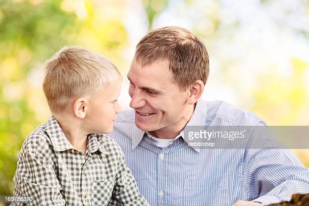young father and son sitting together looking at each other - i love you stock pictures, royalty-free photos & images