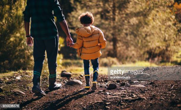 young father and son with rain boots walking in nature - black shoe stock pictures, royalty-free photos & images