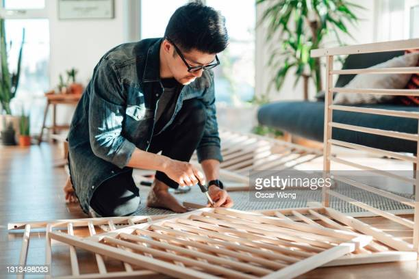 young father assembling baby cot at home - genderblend stock pictures, royalty-free photos & images