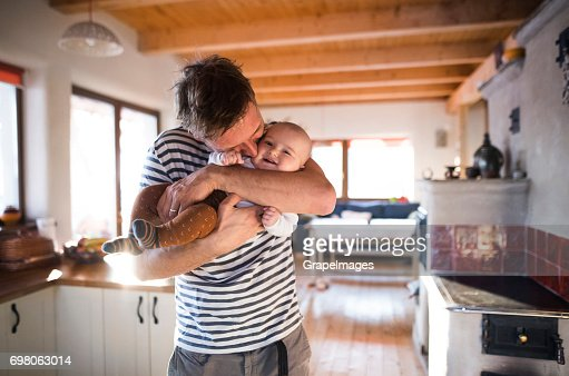 Young father at home in the kitchen holding his baby son in the arms