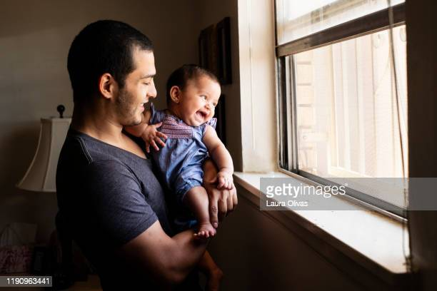 young father being playful with his infant daughter - laura belli foto e immagini stock