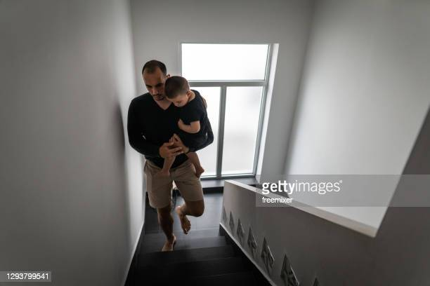 young father carrying his son upstairs - staircase stock pictures, royalty-free photos & images