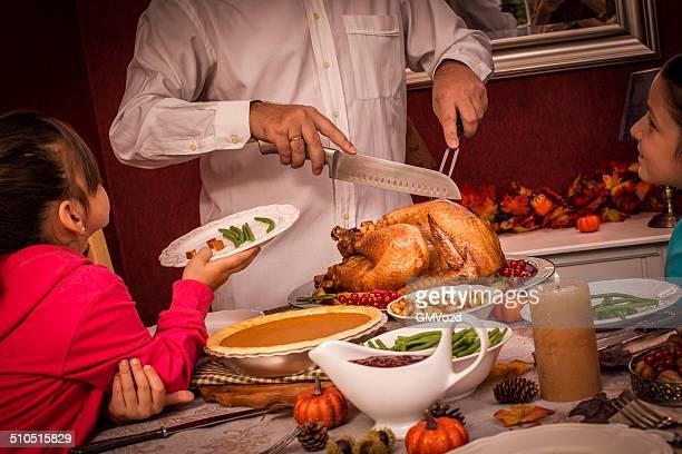 Giovane padre intaglio Turchia alla sua famiglia per la Festa del ringraziamento