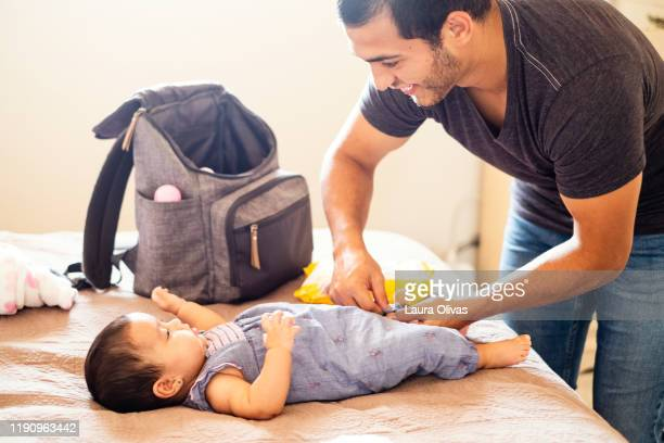 young father changes diaper of his infant daughter - diaper bag stock pictures, royalty-free photos & images
