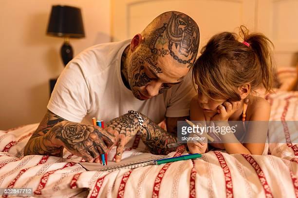 Joven padre con su hija de dibujo en el dormitorio.