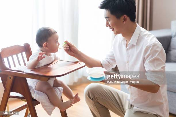 Young father feeding baby