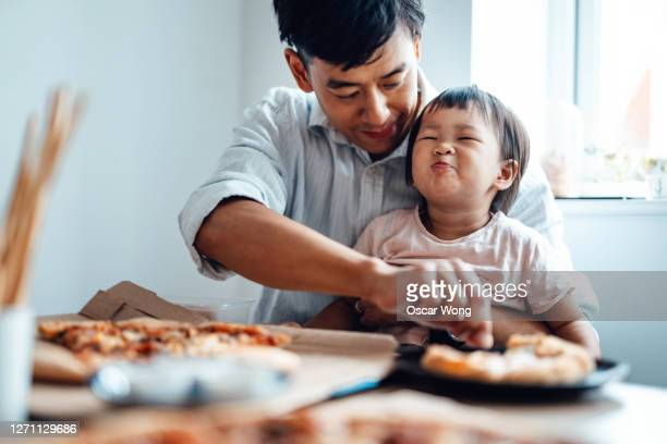 young father feeding food for his baby daughter at the table - genderblend stock pictures, royalty-free photos & images