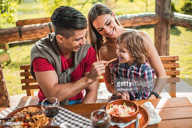 Young father feeding his son with French fries in restaurant.