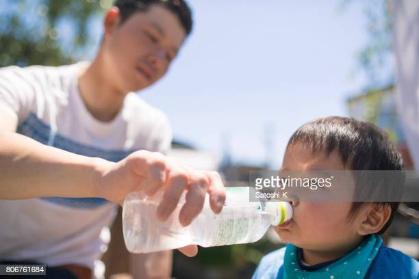 Young father giving water to his baby