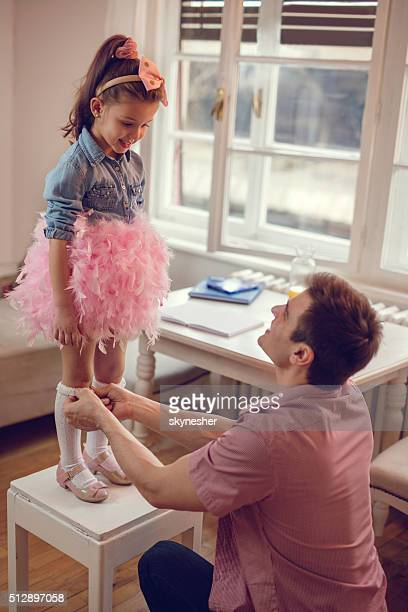Young father helping his little girl to get dressed.