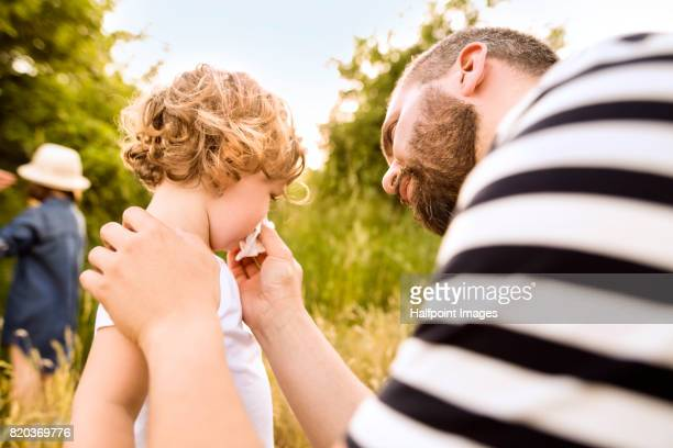 Young father helping little daughter blow her nose.