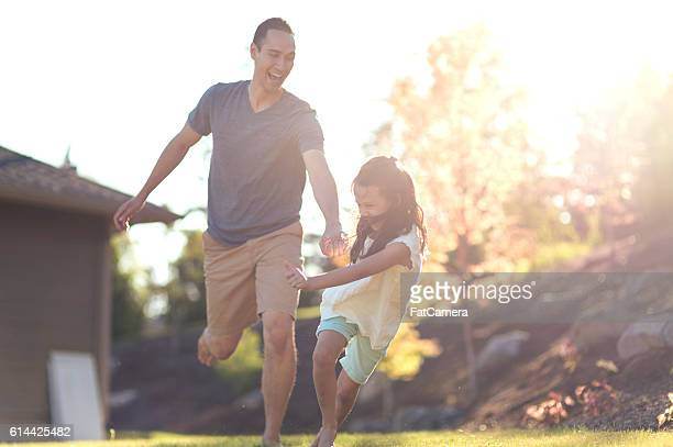 Young father holding hands with his daughter and running