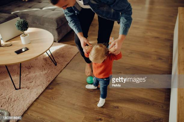 young father is playing with his baby in the living room - beginnings stock pictures, royalty-free photos & images