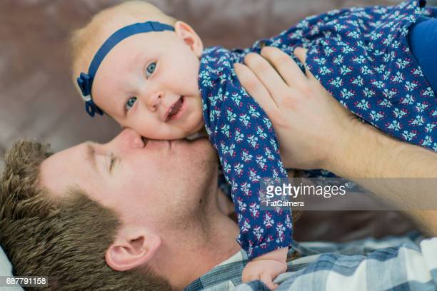 Young Father Kisses his Baby Girl