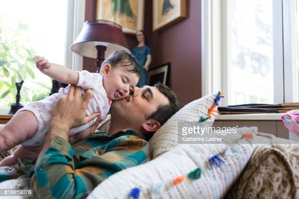 Young father kissing baby daughter