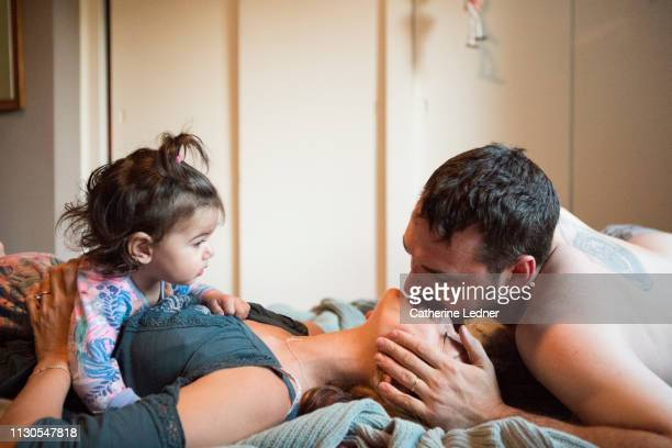 young father kissing wife on forehead as toddler looks on