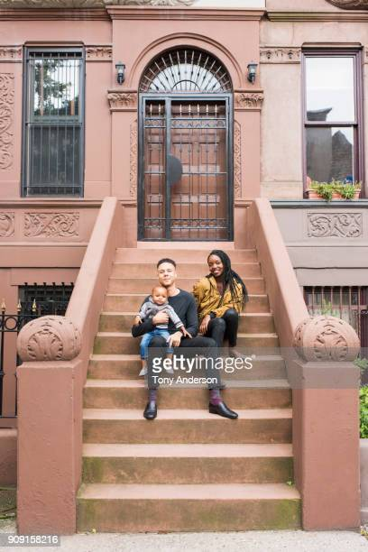 Young father mother and infant daughter on stoop in their city neighborhood