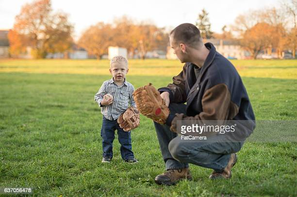 Young father playing with his toddler son in a park