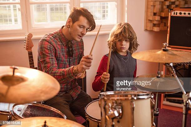 Young father showing his son how to play drums.