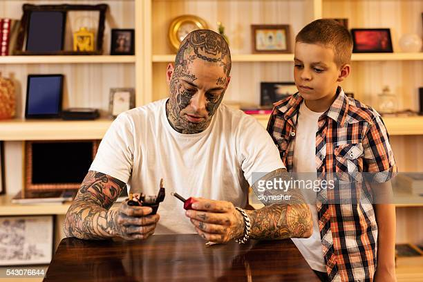 Young father showing his son how to set tattoo gun.