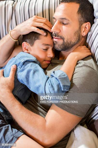 young father spending time together with his 8 years old son, both of mixed race on a couch, the man in his 30s with short dark hair and trimmed beard is hugging his preadolescent boy child while sleeping and relaxing during day. - ems forster productions stock pictures, royalty-free photos & images