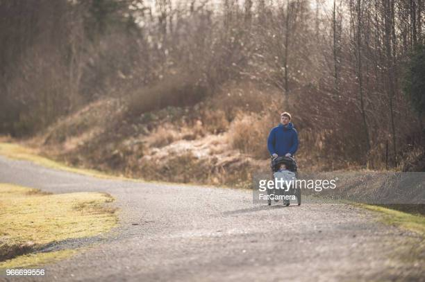 young father takes his toddler son for a nature walk in the stroller - stay at home father stock pictures, royalty-free photos & images