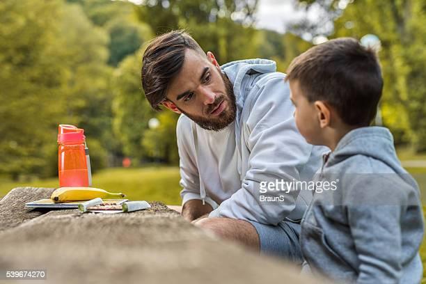 Joven padre hablando con su pequeño hijo en el parque.