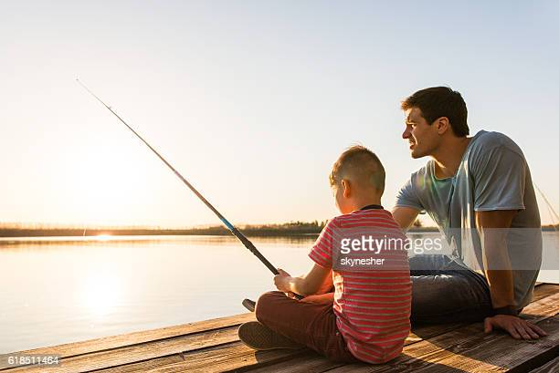 Young father teaching his son to fish on a pier.